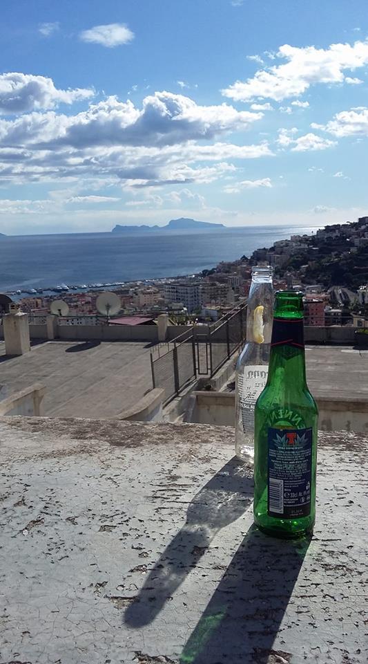 La foto del giorno. Bottiglie vuote e Capri all'orizzonte
